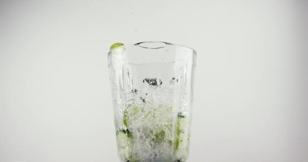 Zelené ovoce a zelenina padající do mixéru s vodou a mletím