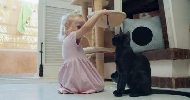 Nettes kleines Mädchen, das der schwarzen Katze zu Hause kleine Fische gibt