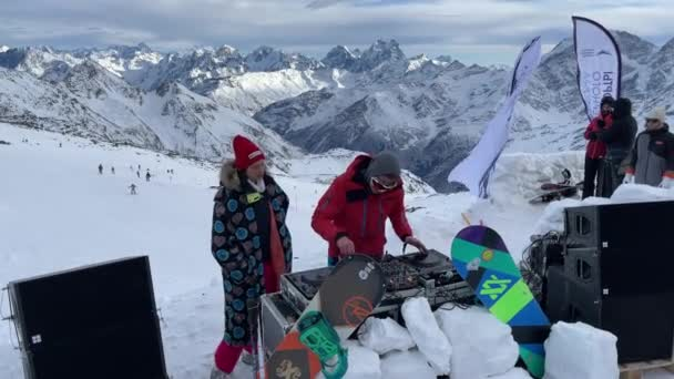 Russia, Kabardino-Balkariya, 07 January 2021: The DJ plays on the most top mark of Mount Elbrus, the girl dances nearby, the mountain on a background, Azaus ski resort