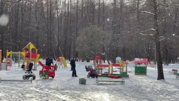 Russland, St.Petersburg, 08. März 2021: Kinderspielplatz im Park am winterklaren Nachmittag, Eltern spielen mit Kindern, es schneit, helle Farbstrukturen, graue Bäume im Hintergrund