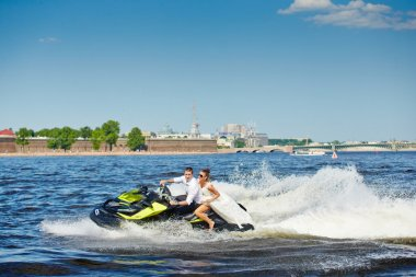 02.06.2013, Russia, Saint-Petersburg: Newlyweds go on jet skis, the bride and groom on the background of Peter and Paul Fortress, the water area of the Neva river, boat, beach, blue sky, sunny weather