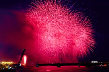 Russia, St. Petersburg, 20.6.2015: Fireworks on the Neva River on a holiday SCARLET SAILS diluted Troitsky Bridge, Rastralnye colony on the Spit of Vasilyevsky Island, a lot of people on the Palace Embankment, water flashes red, white night, holiday