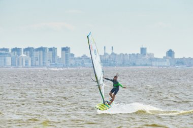 Russia, St. Petersburg, 07.04.2015: prorider Yegor Popretinsky, rus11, Russian champion in windsurfing performs a trick SHAKA, against the backdrop of the city of St. Petersburg Marine Port, ferry ships, the Gulf of Finland