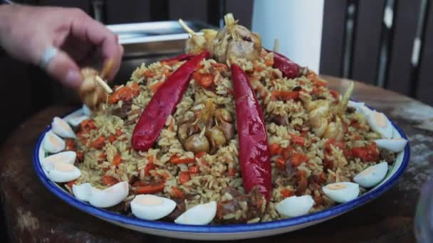 Uzbek national dish pilaf in a large cast-iron cauldron on the fire, on a plate with pilau spread red chili, garlic, quail eggs, carrot, barberry, rice, lamb, mutton fat, the fat tail, sesame oil
