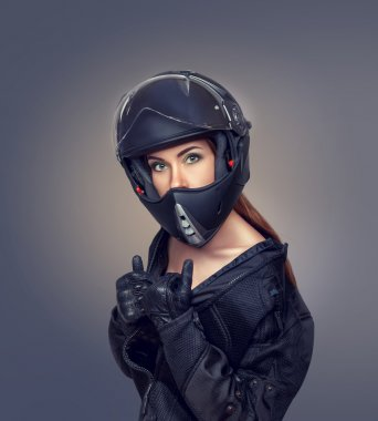 Girl motorcyclist in a black jacket and a helmet