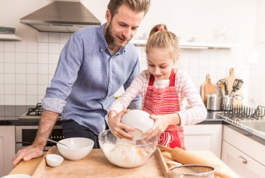 Father and daughter preparing cookie dough in the kitchen