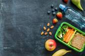 Fotografie School lunch box with sandwich, vegetables, water and fruits
