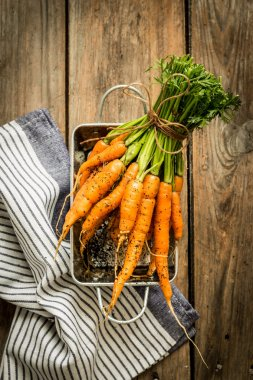 Bunch of young or baby carrots on wooden rural kitchen table