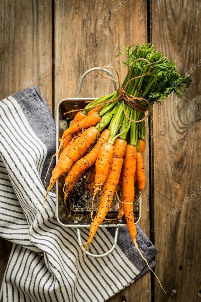 Grupo de jóvenes o zanahorias en la mesa de la cocina rural madera ...