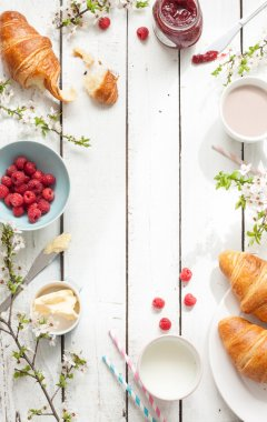 Romantic french or rural breakfast - cocoa, milk, croissants, jam, butter and raspberries