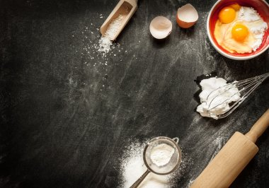 Baking cake ingredients on black chalkboard