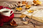 Hot coffee, vintage book, glasses and autumn leaves on wood