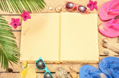 Blank book, sand, sunglasses and flip flops and beach