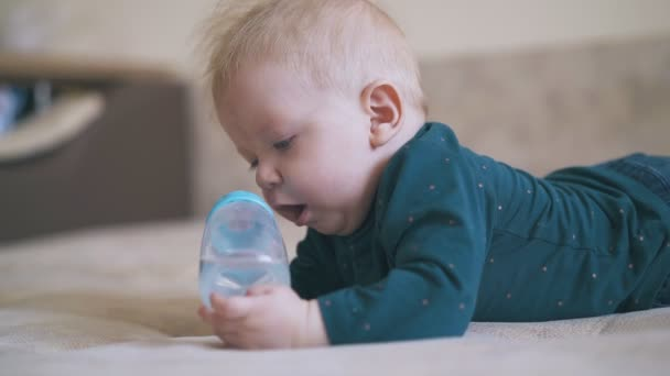 adorable boy nibbles bottle teat lying on soft bed in room