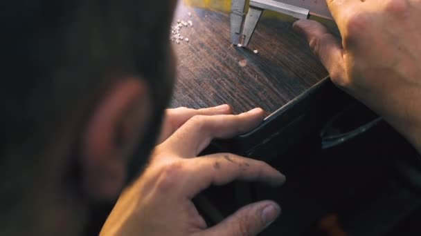 jeweler measures diamonds with ruler on dark table closeup