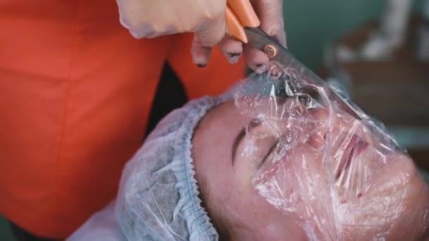 kosmetický střih a vložení fólie na tvář ženy