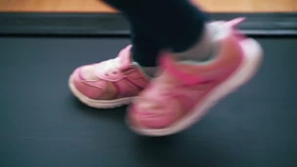 Verspielte Mädchen in rosa Turnschuhen hüpfen zu Hause auf modernem Laufband