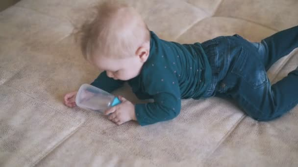 cute child plays with bottle crawling on bed at home