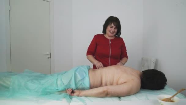 masážní terapeut hovoří se ženou před zákrokem na klinice