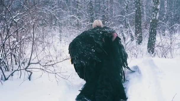 unavená herečka v černých šatech s křídly prochází sněhem
