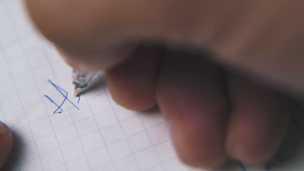 person writes letter to daddy with pen on checkered paper