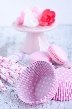 Sugar coated candies, cupcake baking cups, macaroons, pink straws