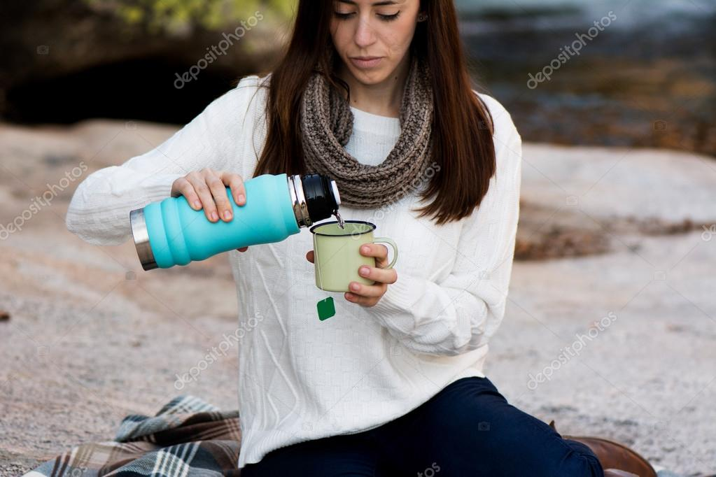 Young woman sitting near the waterfall, with a thermos, and maki