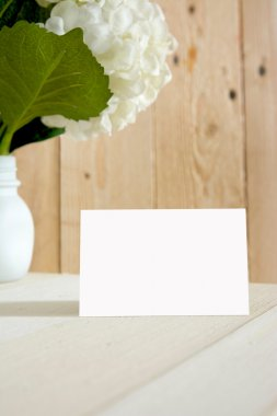 blanck business card, gift box and flowers, sobre fondo a rayas