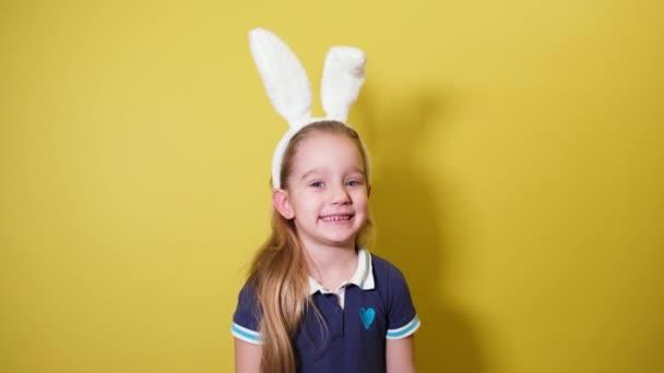 Kleine hübsche Mädchen in weißen Hasenohren lächeln und lachen. Frohe Ostern.