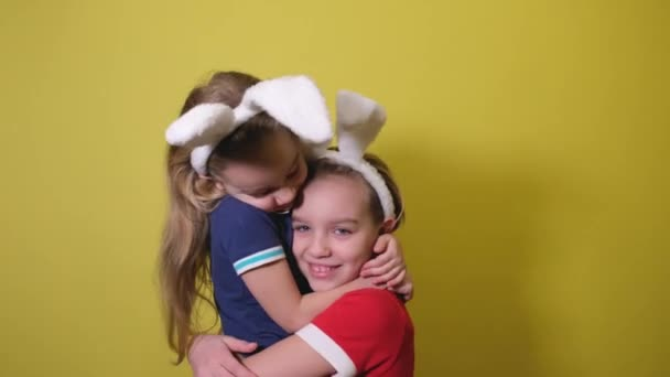 Two sisters or two child girls in white bunny ears Headband smiling and laughing. Happy Easter concept with kids. Two girls in Headband of white bunny ears hugging and laughing