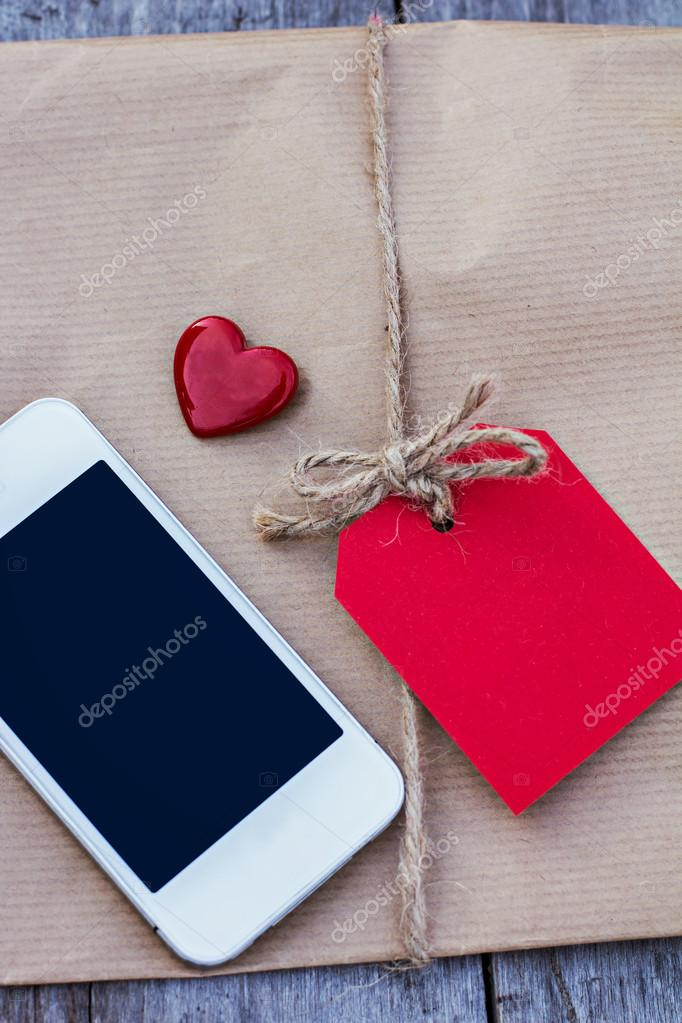 Gift in kraft paper with red card  on a wooden table