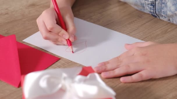 Child hands draws a greeting card and writes I love you in red pencil. Congratulations for Mothers Day or Birthday holiday.