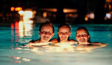 Three kids in illuminated pool