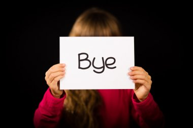 Child holding sign with Spanish word Bye which means See You Lat