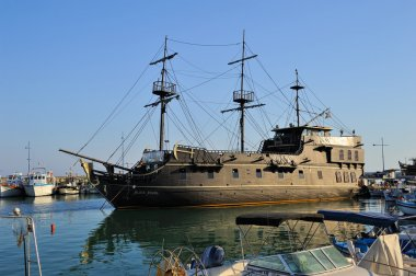 Cyprus, Pleasure boat, a replica of the famous Black Pearl anchored surrounded by fishing boats in the bay of Ayia Napa