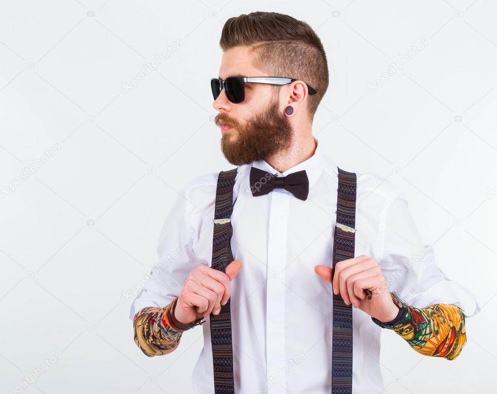 portrait of a stylish hipster holding his suspenders