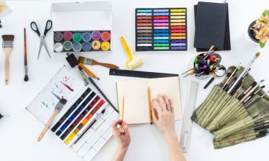 Artist drawing graphic sketch at sketchbook. Workplace, workspace. Top view photo of artistic tools lying on work-table: gouache, crayons palette and paintbrush collection stock vector
