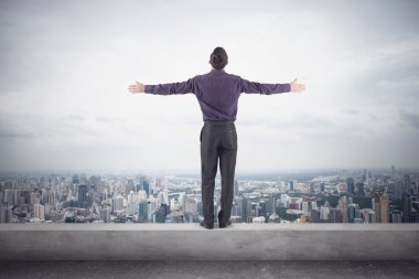 Confident businessman purple shirt and trausers standing on edge of roof with his hands sides front magnificent view city