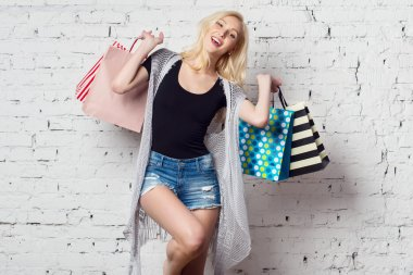 Adorable blond girl against the wall with shopping bags new purchases laughing out loud wearing summer clothes