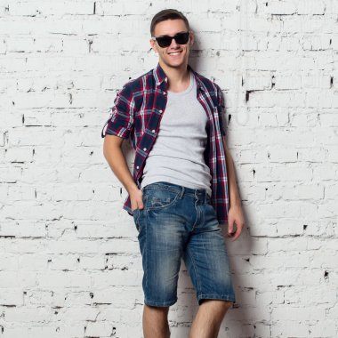 Handsome stylish young man in jeans shorts and shirt. Attractive hipster  with a bristle,sunglasses