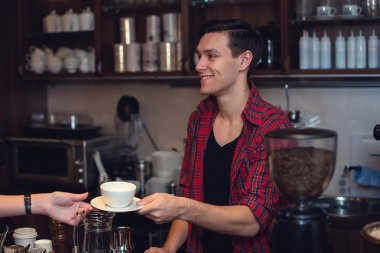 Young hipster working in cafe. Barista is passing an order to a customer smiling.