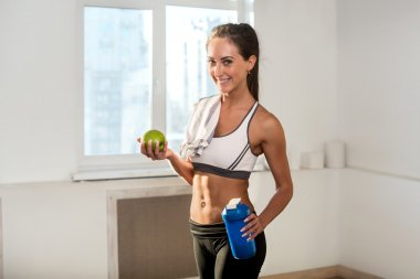 Beautiful fit and slim young athletic sportive woman in sport outfit is smiling holding apple blue shaker after training.