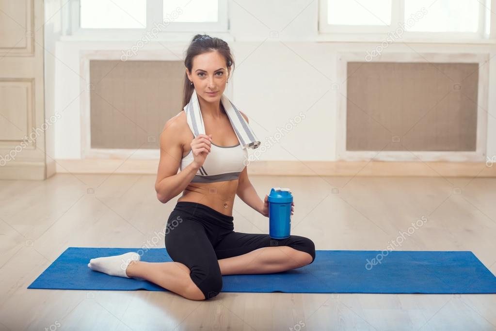 Beautiful athletic sporty woman sitting on yoga mat after some exercises with blue shaker in her hand  and white towel.