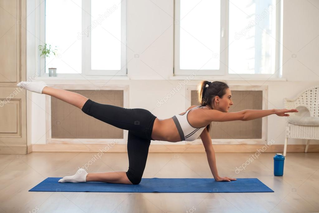 Young dark-haired athletic sporty slim woman doing yoga exercise the gym in front of windows stretching her arm to front.