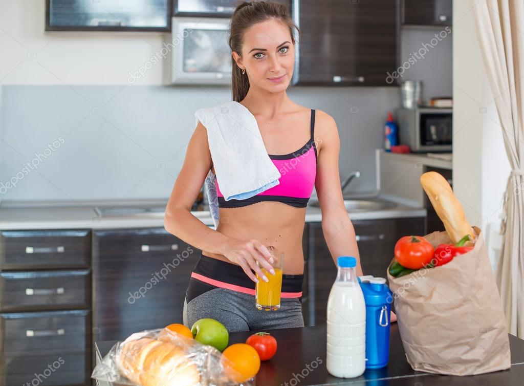 Pretty attractive athletic sportive lady woman standing in kitchen with a towel on her shoulder and healthy food fresh fruits milk bread around drinking cold drink beverage