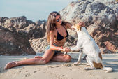 Fotografie Portrait of beautiful happy young woman sitting playing her pet dog at the beach on sea shore