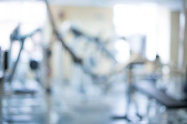 interior of new modern fitness center gym with equipment, abstract blur background.
