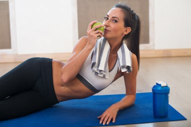 Caucasian beautiful healthy athletic sportive girl eat green apple and Yoga Mat shaker after the training looking at camera.