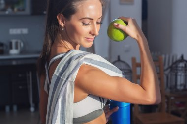Active athletic sportive woman with towel in sport outfit holding apple showing biceps healthy lifestyle