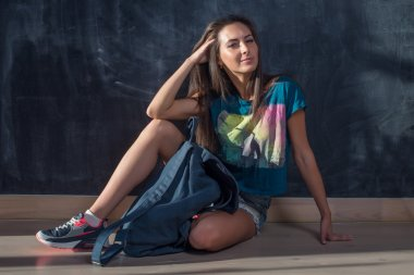 Trendy Hipster Girl in jeans shorts and t-shirt Sitting on floor looking at the camera